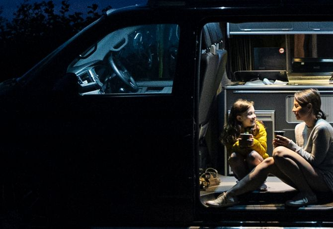 Mother and daughter in campervan at night