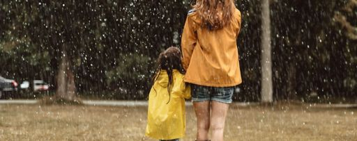 Mother daughter with umbrella in rain