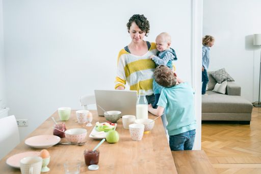 Mother working on a laptop from home with her children