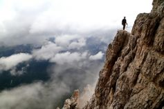 Mountaineer standing on mountain in clouds