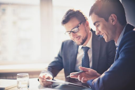 two businessmen using touchpad