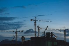 Multiple cranes machines at large construction site at evening