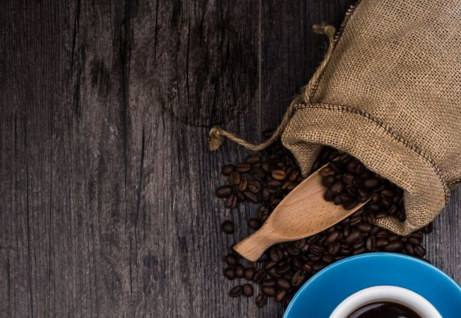 Cup of coffee with scattered coffee grains on wooden background