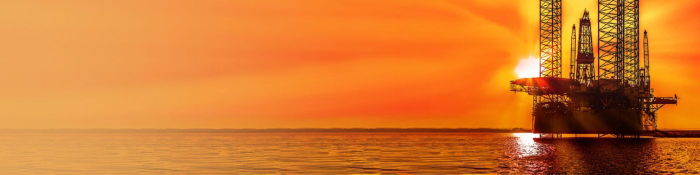 Oil drilling rig in sunset time at sea