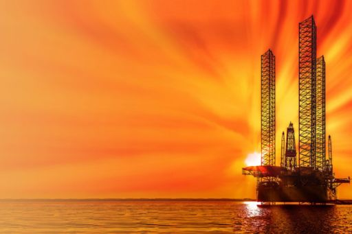 View of oil drilling rig during sunset in ocean