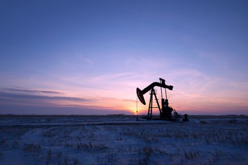 An oil drilling rig and pumpjack on a flat plain