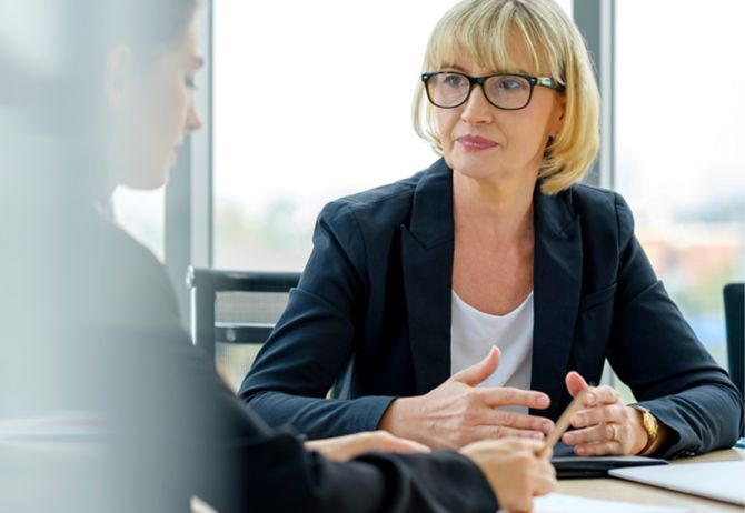 Old woman wearing spectacles in a meeting