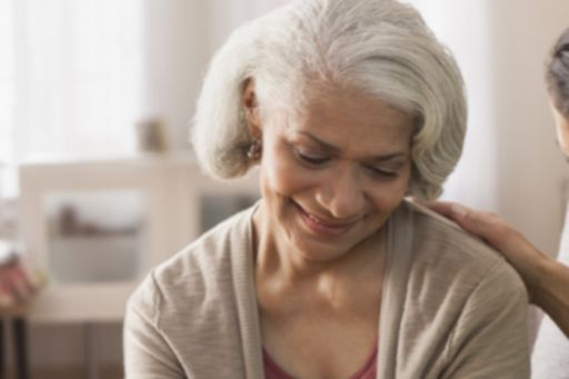 Old woman with grey short hair looking down smiling and sitting on sofa