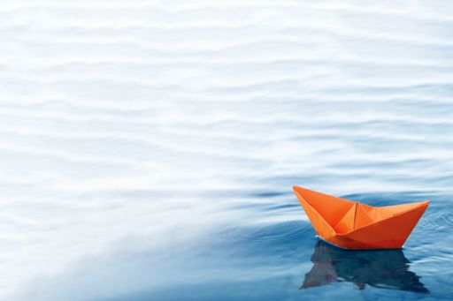 Orange colored paper boat floating in water