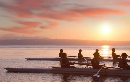 People boating in ocean at sunset