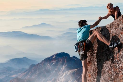 people on mountain cliff helping each other