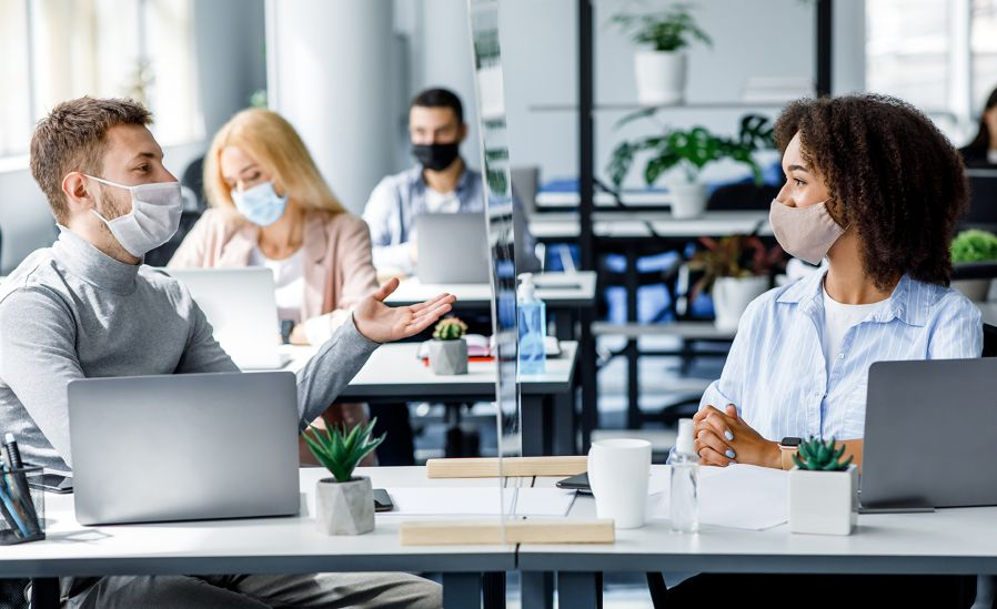People sitting at social distance in office wearing masks