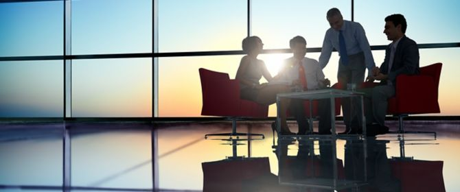 People sitting in a glass room discussing something.