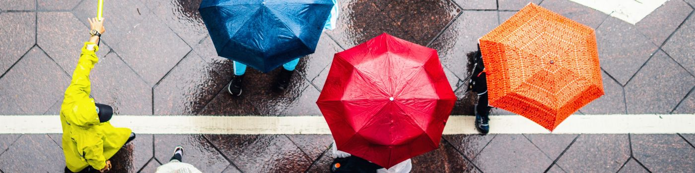 People walking on street with colorful umbrellas