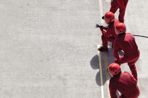 People wearing red uniform and working on road