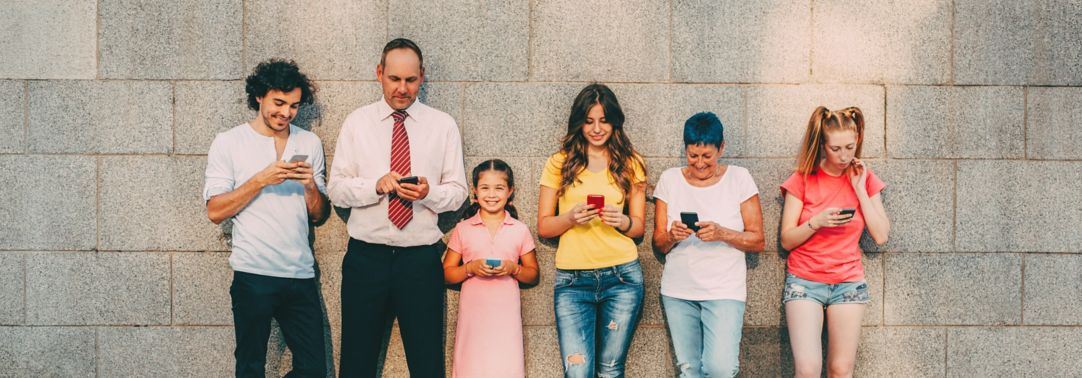 People young and middle aged standing against wall with phones in hand