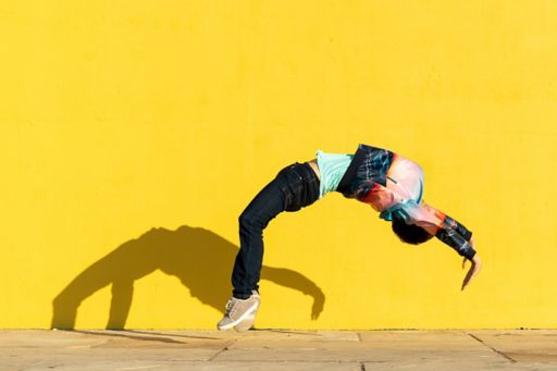 Person doing a backflip against a yellow wall