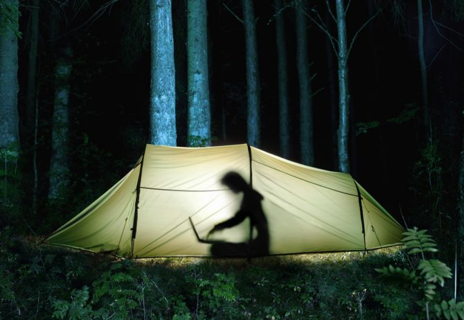 Person inside tent working on laptop in forest at night