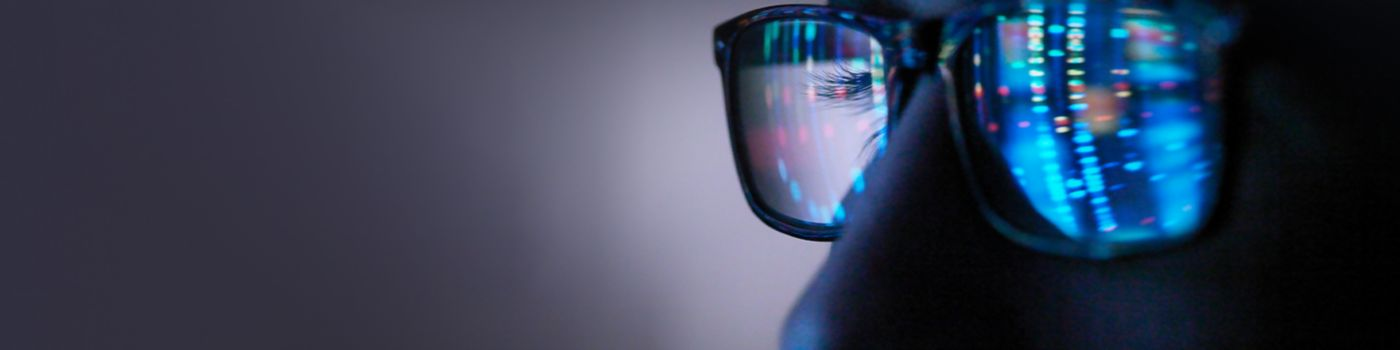 Person looking at screen reflected in their glasses