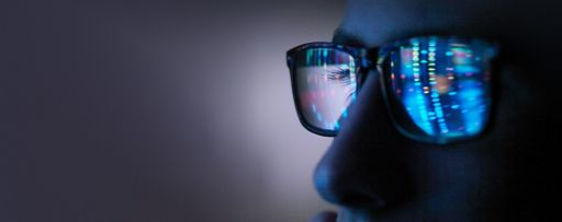 Person looking at a screen reflected in their glasses