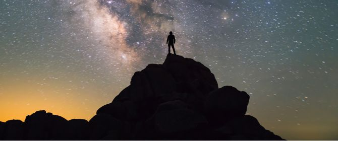 Person standing on a mountain looking at the milky way