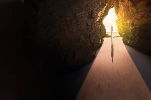 Person standing outside the cave near the seashore in front of sunlight