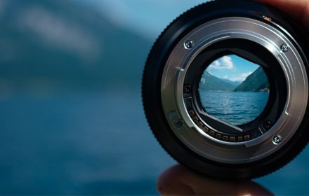 Photo lens in hand viewing blue colored mountain river