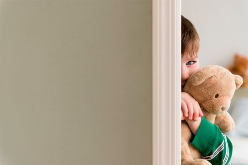 Portrait of boy 4-5 hiding behind the wall