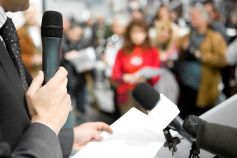 Person holding mic in conference