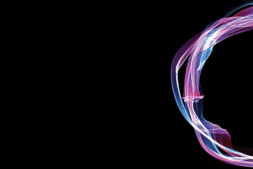 Purple, white and blue fluorescent swirl on a black background