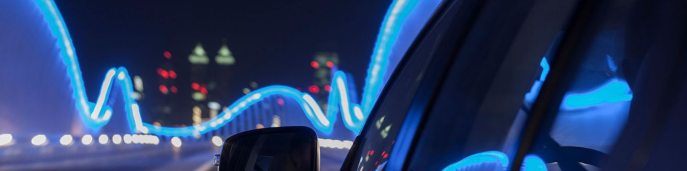 Rear view mirror of car on illuminated bridge