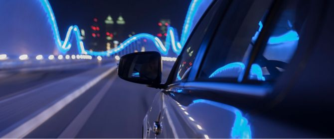 Rear view mirror of car on illuminate bridge