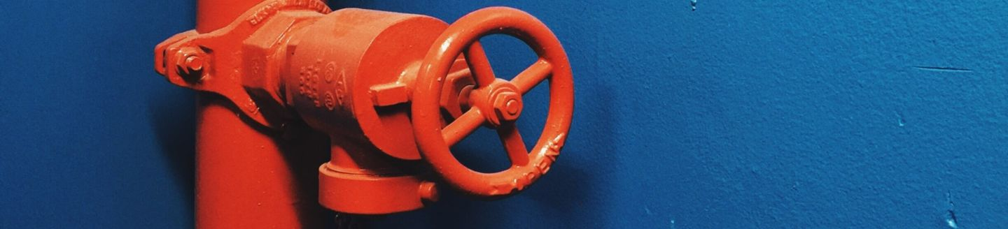 Red Pipeline With Safety Valve Against Blue Wall