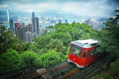 Red train in Hongkong going into trees with city and buildings in background