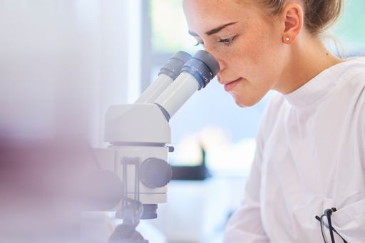 Research scientist looking into a microscope