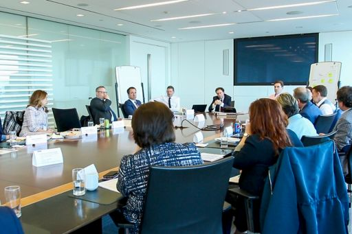 Round table conference with screen on wall
