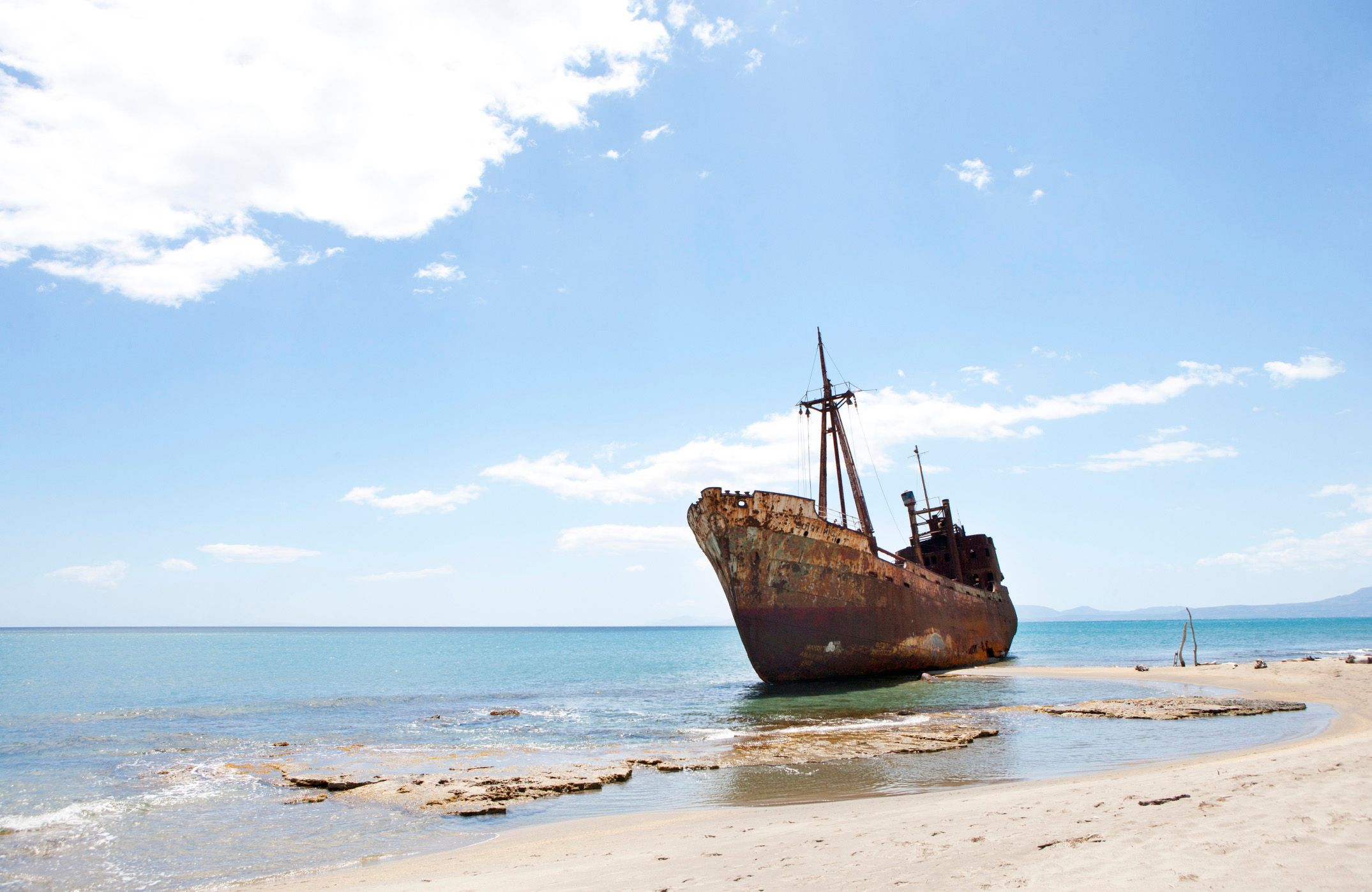 rusting ship and sandy shore