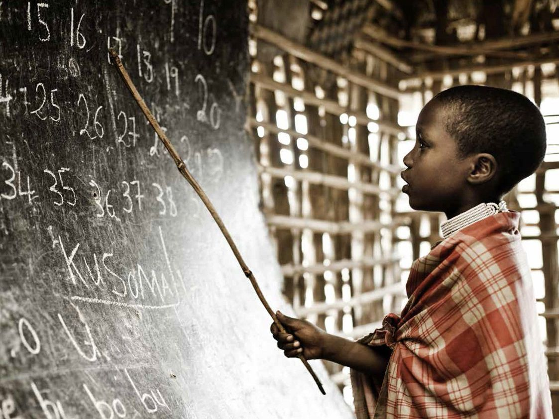 boy solving a problem on a chalkboard