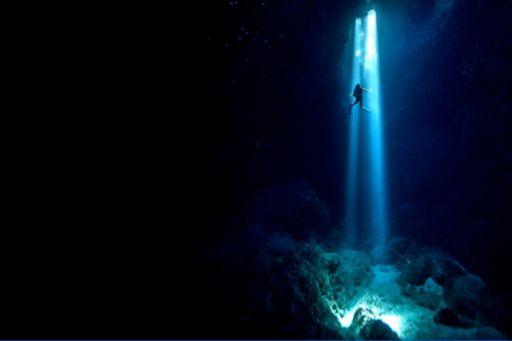 Scuba diver inside cenote swimming up to surface