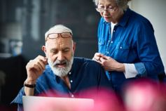senior couple at home working on computer