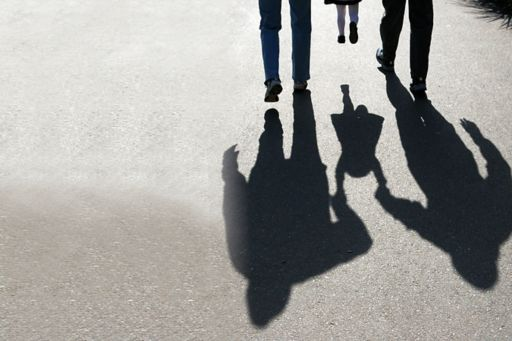 shadows behind two adults carrying a child
