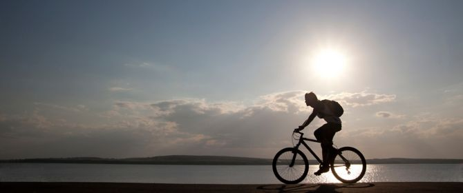 Silhouette of cyclist shape at sunset