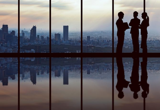 Silhouette of three business people having discussion in office