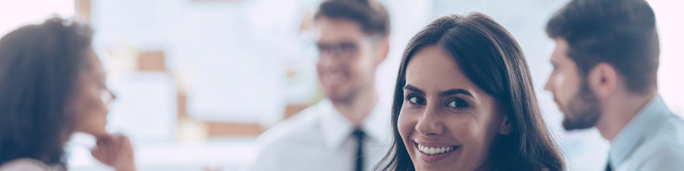 Beautiful cheerful woman looking at camera with smile while sitting at the office table with her coworkers