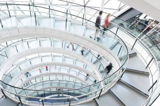 Spiral staircase with people walking down with motion blur