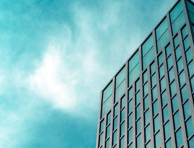 grey skyscraper in front of cloudy blue sky
