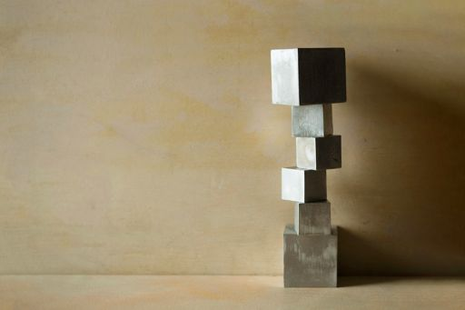 Square aluminium blocks stacked against a beige-coloured wall