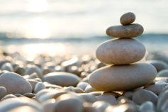 Balancing Stones on Pebble Beach during Sunset