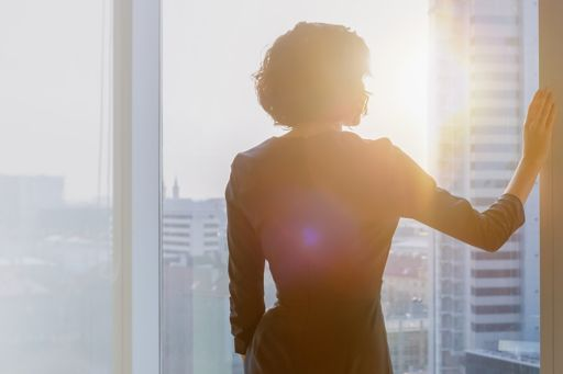 Shot of the successful businesswoman in her office looking out of the window at sunset