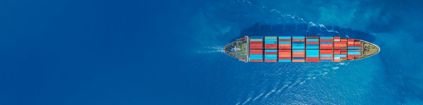 A cargo ship laden with containers travels across the ocean